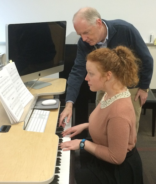 Ken instructs a student on piano.
